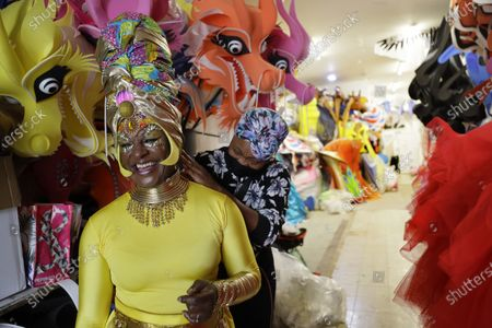 Stock Photo of Anucska Case assists Carolyn Roberts-Griffith, left, with her costume for a prepping event ahead of this years Notting Hill Carnival which will be held virtually, in London, . London's Notting Hill Carnival traces its roots to the emancipation of Black slaves and race riots in the city during the late 1950s. Organizers say the event is more important than ever amid the worldwide campaign for justice following the death of George Floyd in police custody. But their message of resistance and reconciliation will be delivered online worldwide this weekend after the COVID-19 pandemic forced the party to reinvent itself as a virtual event
