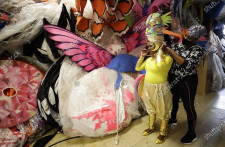 Anucska Case assists Carolyn Roberts-Griffith with her costume for a prepping event ahead of this year's Notting Hill Carnival which will be held virtually, in London, . London's Notting Hill Carnival traces its roots to the emancipation of Black slaves and race riots in the city during the late 1950s. Organizers say the event is more important than ever amid the worldwide campaign for justice following the death of George Floyd in police custody. But their message of resistance and reconciliation will be delivered online worldwide this weekend after the COVID-19 pandemic forced the party to reinvent itself as a virtual event