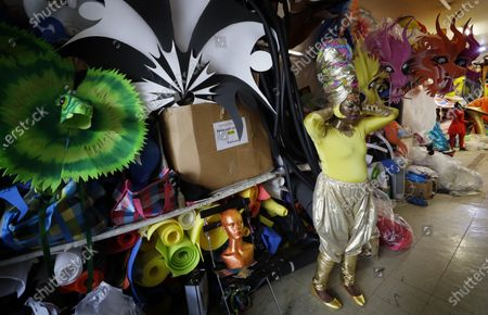 Carolyn Roberts-Griffith adjusts her costume for a prepping event ahead of this year's Notting Hill Carnival which will be held virtually, in London, . London's Notting Hill Carnival traces its roots to the emancipation of Black slaves and race riots in the city during the late 1950s. Organizers say the event is more important than ever amid the worldwide campaign for justice following the death of George Floyd in police custody. But their message of resistance and reconciliation will be delivered online worldwide this weekend after the COVID-19 pandemic forced the party to reinvent itself as a virtual event