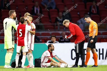Daley Blind (bottom C) of Ajax receives medical assistance after collapsing during a pre-season friendly soccer match between Ajax Amsterdam and Hertha BSC at the Johan Cruijff Arena in Amsterdam, Netherlands, 25 August 2020 (issued on 26 August 2020). Blind, who was diagnosed with a heart condition in December 2019, 'feels good under the circumstances', Dutch Eredivisie soccer club Ajax said on 26 August 2020.