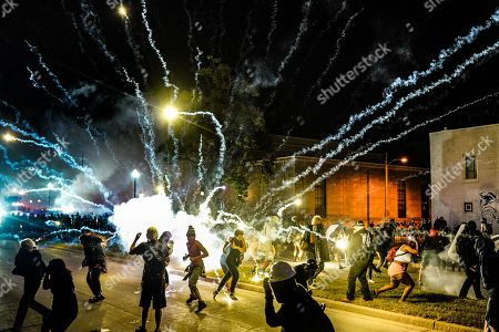 A large firework thrown short of target (police) and lands amongst protesters.