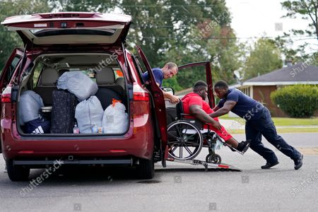 Lake Charles Fire Department personnel Alvin Taylor, right, and Jeremy Harris, left, assist Tim Williams into a transport van as he evacuates Lake Charles, La., ahead of Hurricane Laura