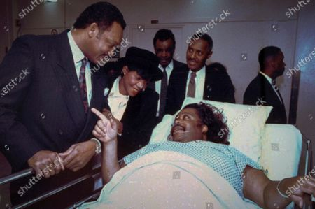 The Rev. Jesse Jackson, left, singer Melba Moore, second from left, union leader Jim Bell, center, and the Rev. Herbert Daughtry, second from right, visiting with the Rev. Al Sharpton in a New York hospital, recovering from a knife attack a day earlier as he prepared to lead protest in the Bensonhurst area of the Brooklyn borough of New York, where Black teenager Yusuf Hawkins was fatally shot. For more than three decades, Sharpton, 65, has been a go-to advocate for Black American families seeking justice and peace in the wake of violence and countless incidents that highlight systemic racism