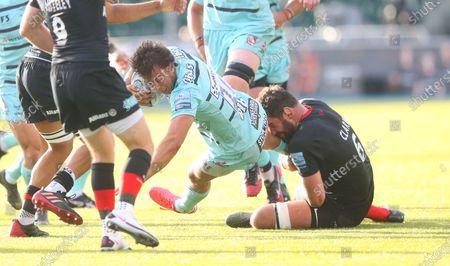 Lloyd Evans of Gloucester tackled by Calum Clark of Saracens