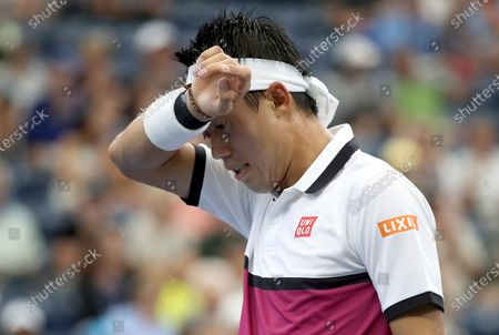 """Kei Nishikori, of Japan, wipes sweat from his brow between serves from Bradley Klahn during the second round of the U.S. Open tennis championships in New York. Nishikori, the 2014 U.S. Open runner-up, said he tested negative for COVID-19 after having two positive tests but still decided to withdraw from the Grand Slam tournament that begins next week. Nishikori wrote, on his mobile app that he is ready to """"slowly"""" return to practice - but not prepared to compete in best-of-five-set matches"""