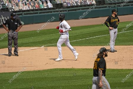 Stock Photo of Chicago White Sox's Eloy Jimenez, center, rounds the bases after hitting a three-run home run as Pittsburgh Pirates third baseman JT Riddle, right, top, and starting pitcher Trevor Williams looks to the field during the fifth inning of a baseball game in Chicago