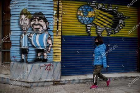 Mural features Lionel Messi, left, and Diego Maradona, in an embrace, painted on a corner column in Buenos Aires, Argentina, . Messi has told Barcelona he wants to leave the soccer club after nearly two decades with the Spanish giants. The club has confirmed that the Argentina great has sent a note expressing his desire to leave