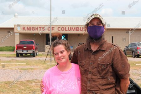 Stock Photo of James and Samantha Bison, pose for a photo, by their car outside the Knights of Columbus hall in Ennis, Texas where they've been evacuated to after leaving their home in Jasper, Texas, as Hurricane Laura is approaching that area. They were directed to Ennis by a 211 information line. Hoping for a place to stay, they ended up sleeping in their car. When they called 211 again, an operator told them to drive to San Antonio, about 250 miles (400 kilometers) in a different direction