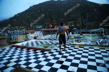 Stock Image of Nestor Serrano walks on the upstairs floor of his home, where the walls were blown off, in the aftermath of Hurricane Maria, in Yabucoa, Puerto Rico. Nasty hurricanes that cause billions of dollars in damage are hitting more often. Laura, which is threatening the U.S. Gulf Coast, is only the latest