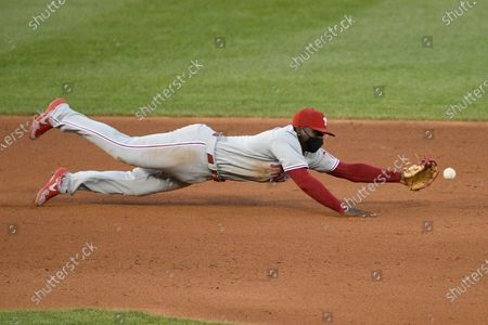 Philadelphia Phillies shortstop Didi Gregorius dives for but misses the ball on a single by Washington Nationals' Howie Kendrick during the fourth inning of a baseball game, in Washington