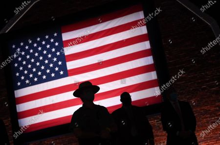Stock Photo of A U.S. Park Ranger is silhouetted against the American flag wait on the third night of the Republican Nationals Convention at Ft. McHenry in Baltimore, Maryland.
