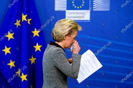 President of the European Commission Ursula von der Leyen puts on her protective face mask as she leaves the podium after a media conference at EU headquarters in Brussels, . The European Commission president said Thursday her team could face a reshuffle after the resignation of the Irish trade Commissioner, Phil Hogan, over a controversy involving his questionable adherence to COVID-19 rules