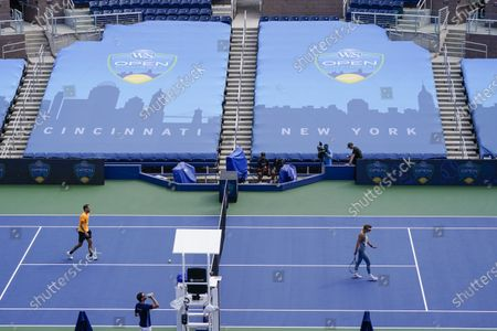 Victoria Azarenka, of Belarus, right, take the court at Grandstand to practice at the Western & Southern Open tennis tournament at the Billie Jean King National Tennis Center, in New York. The tournament was put on hold for a day in a call for racial justice Thursday after Jacob Blake, a Black man, in Wisconsin was shot by police