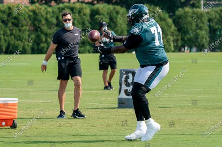 Stock Photo of Philadelphia Eagles tackle Jason Peters catches the ball from executive Connor Barwin during an NFL football practice, in Philadelphia