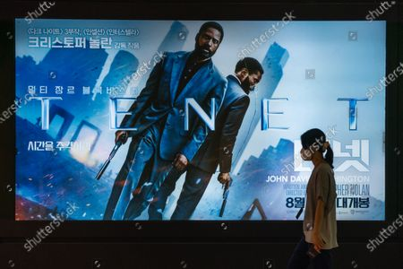 A woman wearing protective mask walks by a billboard of the movie 'TENET'. Movie 'TENET' directed by Christopher Nolan is released on 26 August in South Korea for the first time in the world.