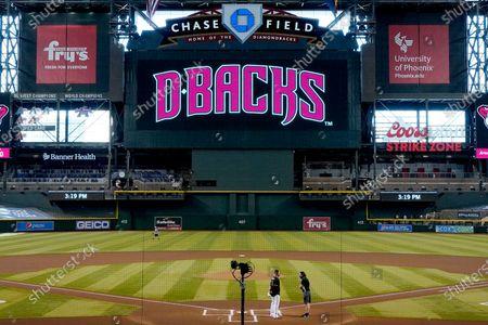 Arizona Diamondbacks' Nick Ahmed, left, talks with Colorado Rockies' Daniel Murphy after the Rockies decided not to play their baseball game against the Diamondbacks, in Phoenix