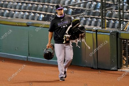 Colorado Rockies bullpen catcher Aaron Munoz walks to the clubhouse after the team decided not to play their baseball game against the Arizona Diamondbacks, in Phoenix
