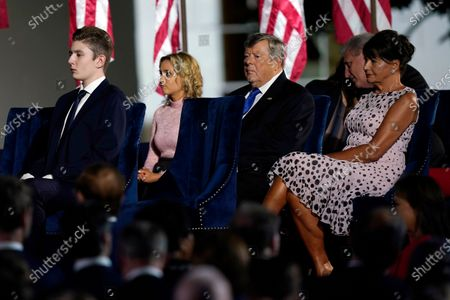 Barron Trump, left, and Viktor Knavs and Amalija Knavs, parents of Melania Trump, sit before President Donald Trump speaks from the South Lawn of the White House on the fourth day of the Republican National Convention, in Washington