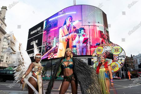 Stock Image of A trio of Caribbean soca dancers, Andrea Wallace, Fiona Compton, Donna Cupid-Thuesday, entertain passers-by as Samsung unveil on the iconic Piccadilly Circus screens a trailer for the first ever digital Notting Hill Carnival, London. Picture date: Friday August 28, 2020. The exclusive trailer, shot by Samsung entirely in 8K using their S20 devices, will continue to play every hour throughout the day before the digital event starts online at the official Notting Hill Carnival website. The trailer is also available to watch via QLED 8K at Samsung KX in Coal Drops Yard, Kings Cross this Bank Holiday weekend.