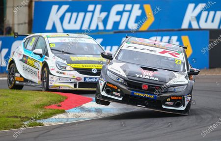 Dan Cammish lifts his car off the ground on the curbs as he is pursued by Mike Bushell; Knockhill Racing Circuit, Fife, Scotland; Kwik Fit British Touring Car Championship, Knockhill, Qualifying Day.