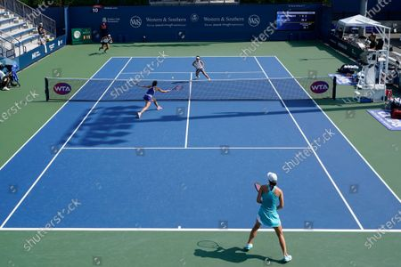 Iga Swiatek, of Poland, front right, watches as teammate Viktoria Kuzmova, of Slovakia, front left, returns a shot during their doubles match with Nicole Melichar, top left, and Yifan Xu, of China,top right, during the semifinals at the Western & Southern Open tennis tournament, in New York