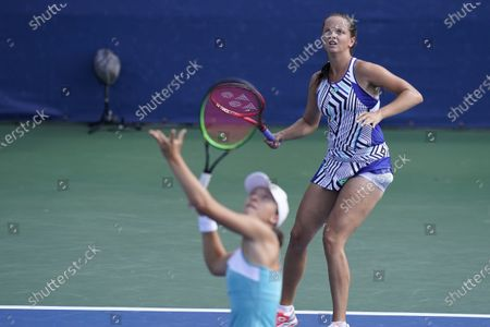 Iga Swiatek, of Poland, front, looks to hit the ball as teammate Viktoria Kuzmova, of Slovakia, right, backs her up during their doubles match with Nicole Melichar and Yifan Xu, of China, during the semifinals at the Western & Southern Open tennis tournament, in New York