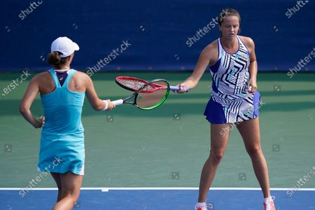 Stock Photo of Iga Swiatek, of Poland, left, taps her racquet with teammate Viktoria Kuzmova, of Slovakia, right, during their doubles match with Nicole Melichar and Yifan Xu, of China, during the semifinals at the Western & Southern Open tennis tournament, in New York