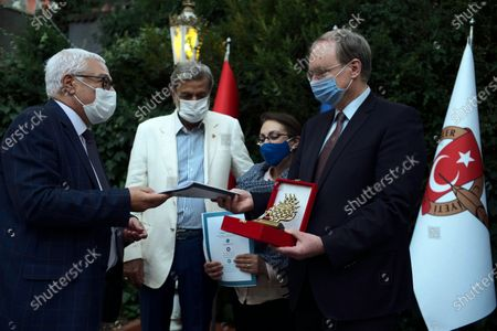 Christian Berger, EU ambassador to Turkey, right, Turkish journalists Yusuf Kanli, left, and Nazmi Bilgin, second left, and Marilena Georgiadou-Berger wearing face masks to protect against the spread of coronavirus, attend a ceremony for journalists, in Ankara, Turkey, . Turkey has recorded the highest number of COVID-19 deaths in a day since May. Health Minister Fahrettin Koca said Friday that 36 people have died of the coronavirus in the past 24 hours, raising the total number of fatalities in the country to 6,245