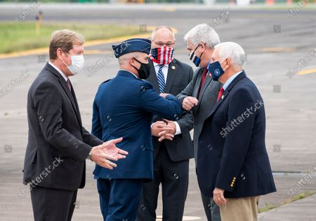 Vice President Mike Pence, right, visits with Rep. Jason Lewis and Rep. Tom Emmer bumps elbows with Minn. Air National Guard Commander Chris Blomquist after arriving at at the Duluth International Airport for a campaign stop in Duluth, Minn
