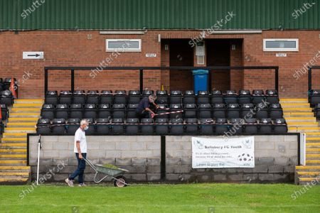 Stock Photo of Volunteer groundsman Peter Robinson and maintenance volunteer John Harper tape off seating during preparations ahead of phase two of crowds being welcomed back into sporting events at The Raymond McEnhill Stadium in Salisbury, Wilts.  Inline with the governments easing of lockdown restrictions, Salisbury Football Club are preparing to welcome back 30% of their fans as of this Monday, August 31st which will be around 600.   Salisbury FC play in Southern League Premier Division South, or step 3 of the non-league football ladder.