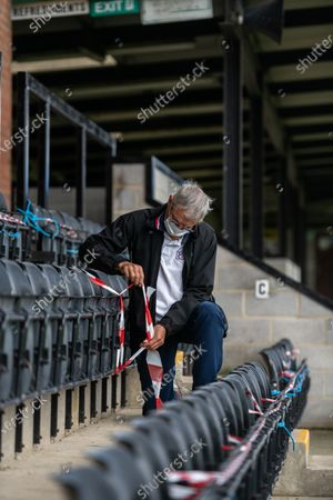 Stock Image of Volunteer groundsman Peter Robinson tapes off seating to comply with social distancing measures during preparations ahead of crowds being welcomed back into sporting events at The Raymond McEnhill Stadium in Salisbury, Wilts.  Inline with the governments easing of lockdown restrictions, Salisbury Football Club are preparaing to welcome back 30% of their fans as of this Monday, August 31st.   Salisbury FC play in Southern League Premier Division South, or step 3 of the non-league football ladder.