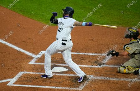 Colorado Rockies' Matt Kemp, left, follows the fliught of his three-run home run with San Diego Padres catcher Austin Hedges in the first inning of a baseball game, in Denver