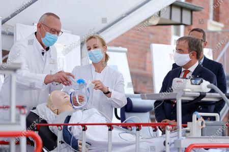 Stock Image of Head physician pneumology Thomas Voshaar and Senior physician internal medicine Daniela Kuehle run a demonstration for North Rhine-Westphalia Governor Armin Laschet and German Health Minister Jens Spahn (not pictured) during a visit in a tent used for coronavirus testing at the Bethanien hospital. Germany is wrestling with a sharp upswing in coronavirus infection rates that authorities attribute to vacationers returning from trips abroad.