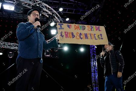 """Comedian Rob Schneider, left, holds up a sign given to him by a fan as he performs with David Spade at """"Comedy In Your Car"""" at the Ventura County Fairgrounds, Friday, Aug. 28. 2020, in Ventura, Calif"""