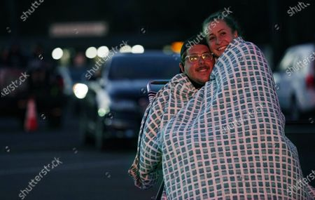 """Jason Bader, left, and his wife Jimmie watch """"Comedy In Your Car"""" with comedians David Spade and Rob Schneider at the Ventura County Fairgrounds, Friday, Aug. 28. 2020, in Ventura, Calif"""