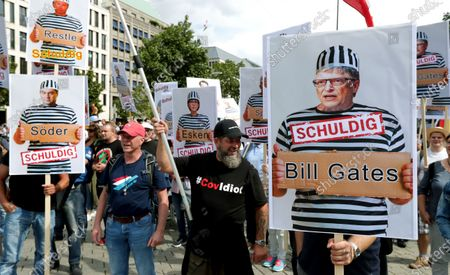 "Stock Picture of People attend a protest rally in Berlin, Germany, against new coronavirus restrictions in Germany, holding a sign with Bill Gates in prison clothes, reading ""Guilty"". Police in Berlin have requested thousands of reinforcements from other parts of Germany to cope with planned protests at the weekend by people opposed to coronavirus restrictions"