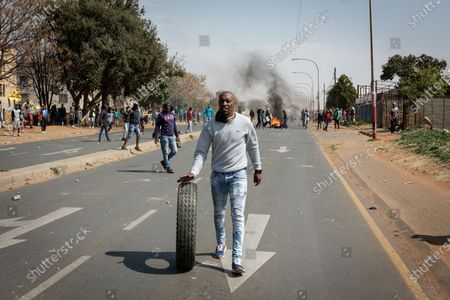 A protestor takes part in a protest over the death of a teenager in Eldorado Park, Johannesburg, South Africa, Aug. 27, 2020. South African President Cyril Ramaphosa on Friday sent condolences to the family of Nathaniel Julius, a 16 year-old boy allegedly killed by the police this week. It is alleged that Nathaniel Julius left home searching for food early this week and was shot dead by the police.