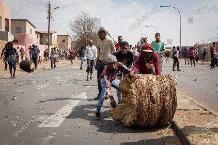 People prepare to barricade a road during a protest over the death of a teenager in Eldorado Park, Johannesburg, South Africa, Aug. 27, 2020. South African President Cyril Ramaphosa on Friday sent condolences to the family of Nathaniel Julius, a 16 year-old boy allegedly killed by the police this week. It is alleged that Nathaniel Julius left home searching for food early this week and was shot dead by the police.