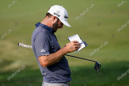 Dustin Johnson looks in his yardage book on the 18th green during the third round, for the BMW Championship golf tournament at the Olympia Fields Country Club in Olympia Fields, Ill. Johnson and Hideki Matsuyama, of Japan, are tied for the lead at 1-under par after three rounds
