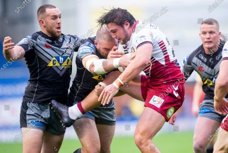 Wigan's Liam Byrne is tackled by Castleford's Daniel Smith & Grant Millington.