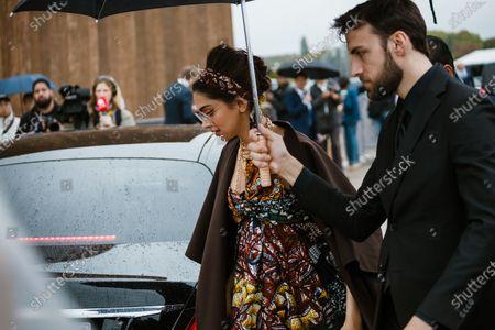 Deepika Padukone wears a colorful African wax hair scarf, necklaces, a dark brown long light coat, a colorful African wax draped bustier gathered long dress, a black Dior clutch, seen outside Dior show during Paris Fashion Week Womenswear Spring Summer 2020