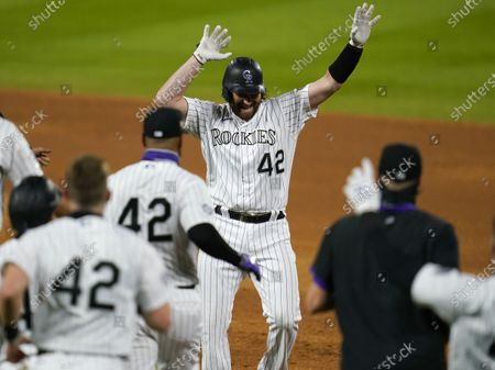 Colorado Rockies pinch-hitter Daniel Murphy, top, celebrates after his walkoff RBI-single off San Diego Padres relief pitcher Craig Stammen in the ninth inning of a baseball game, in Denver