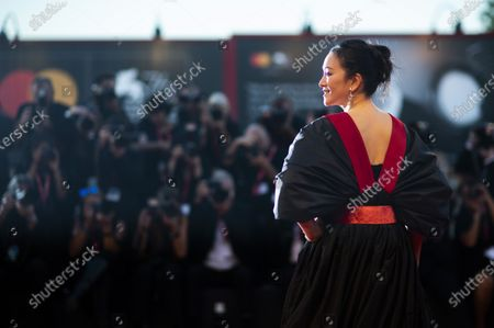 Stock Image of File - Actress Gong Li poses for photographers upon arrival at the premiere of the film 'Saturday Fiction' at the Venice Film Festival. The 77th Venice Film Festival will kick off, but this year's edition will be unlike any others. Coronavirus restrictions will mean fewer Hollywood stars, no crowds interacting with actors and other virus safeguards will be deployed