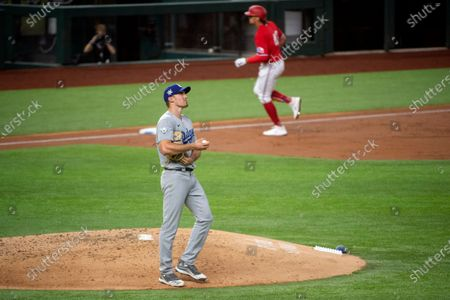 Los Angeles Dodgers starting pitcher Ross Stripling, foreground, looks up after giving up a solo home run to Texas Rangers' Ronald Guzman, background, during the third inning of a baseball game, in Arlington, Texas