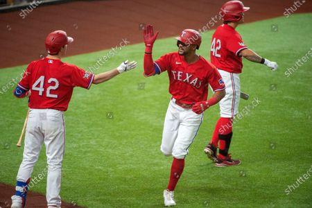 Texas Rangers' Leody Taveras, center, is congratulated by Nick Solak, left, and Shin-Soo Choo after hitting a solo home run off Los Angeles Dodgers starting pitcher Ross Stripling during the third inning of a baseball game, in Arlington, Texas