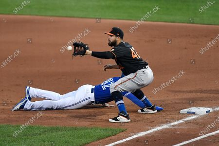 Baltimore Orioles first baseman Renato Núñez, top, reaches for a pickoff attempt as Toronto Blue Jays' Derek Fisher dives safely back to first during the fourth inning a baseball game in Buffalo, N.Y