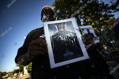 A man holds a picture of late US actor Chadwick Boseman during a vigil to honor his memory in Leimert Park, Los Angeles, California, USA, 29 August 2020. Chadwick Boseman passed away, age 43, after a four year battle with colon cancer.