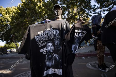 A man sells t-shirts of late US actor Chadwick Boseman during a vigil to honor his memory in Leimert Park, Los Angeles, California, USA, 29 August 2020. Chadwick Boseman passed away, age 43, after a four year battle with colon cancer.