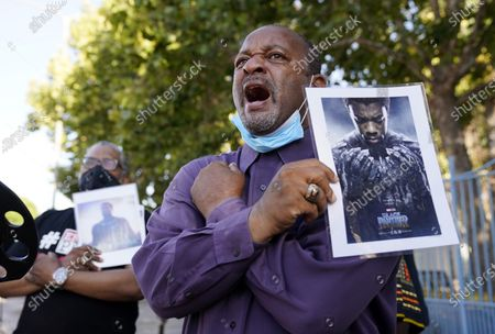 """Najee Ali, director of Project Islamic Hope, leads a """"Wakanda Forever!"""" salute from the 2018 film """"Black Panther,"""" during a news conference to celebrate the late actor and """"Black Panther"""" star Chadwick Boseman, Saturday, Aug. 29. 2020, in Los Angeles. Boseman died Friday at 43 after a four-year fight with colon cancer"""