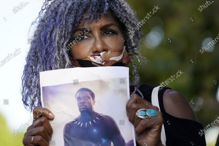 """Artist Kim Maxwell holds a picture of the late actor Chadwick Boseman during a news conference to celebrate his life, Saturday, Aug. 29. 2020, in Los Angeles. The star of such films as """"Black Panther"""" and """"42"""" died Friday at 43 after a four-year fight with colon cancer"""